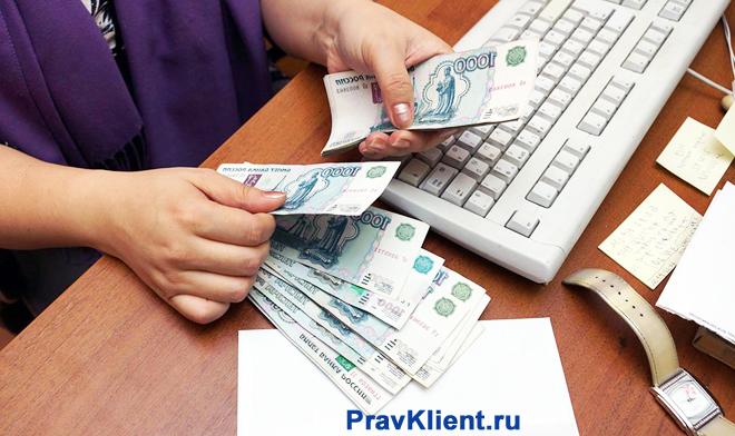 Девушка пересчитывает денежные купюры за компьютерным столом