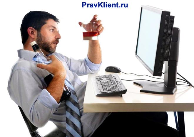 Мужчина выпивает вино на рабочем месте, за компьютером
