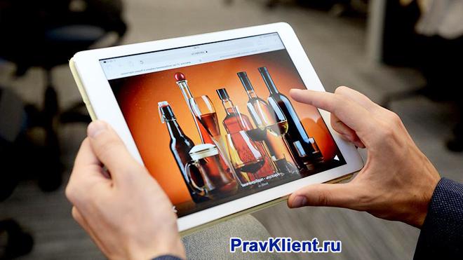 Мужчина выбирает на планшете алкоголь