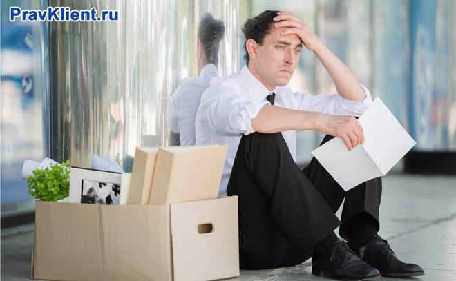 Озадаченный мужчина сидит на улице, рядом стоят картонные коробки