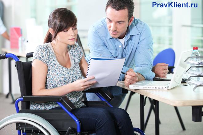 Девушка в инвалидном кресле и ее коллега читают записи в тетради вместе