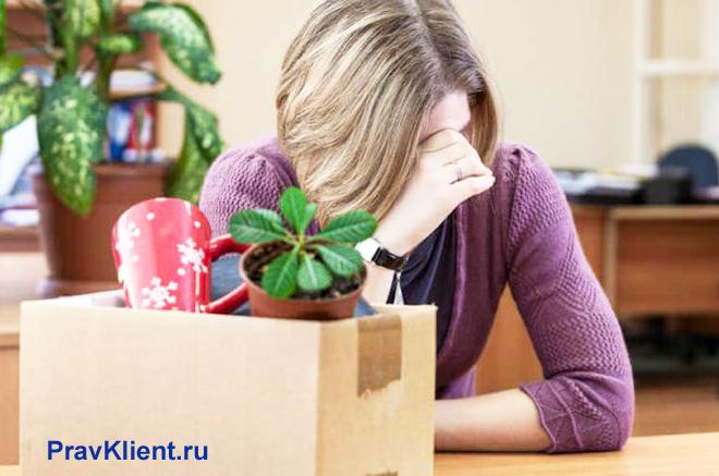 Расстроенная девушка сидит за столом, рядом стоит картонная коробка с вещами