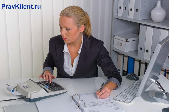 Офисный работник считает на калькуляторе