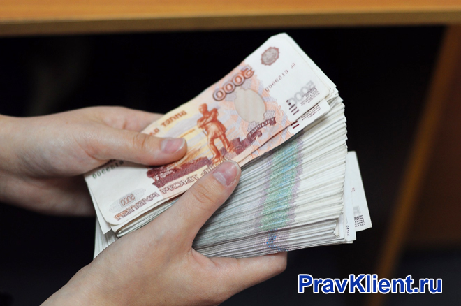 Мужчина держит в руках большую сумму денег