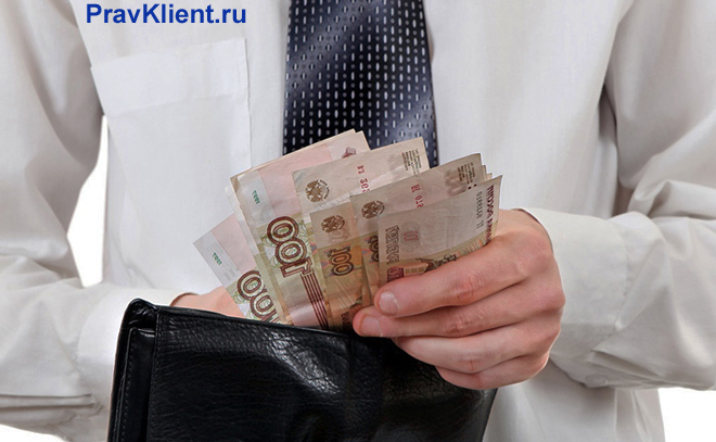 Офисный работник считает в руках деньги