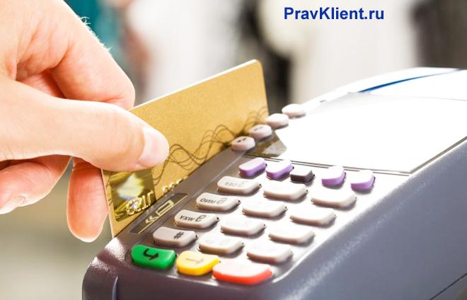 Мужчина оплачивает покупку через банковский терминал