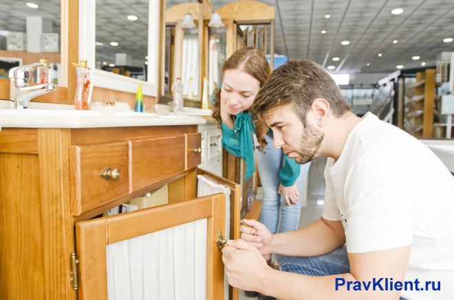 Семейная пара рассматривает шкаф в магазине мебели