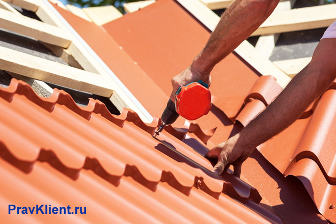 Мужчина укладывает металлочерепицу на крышу