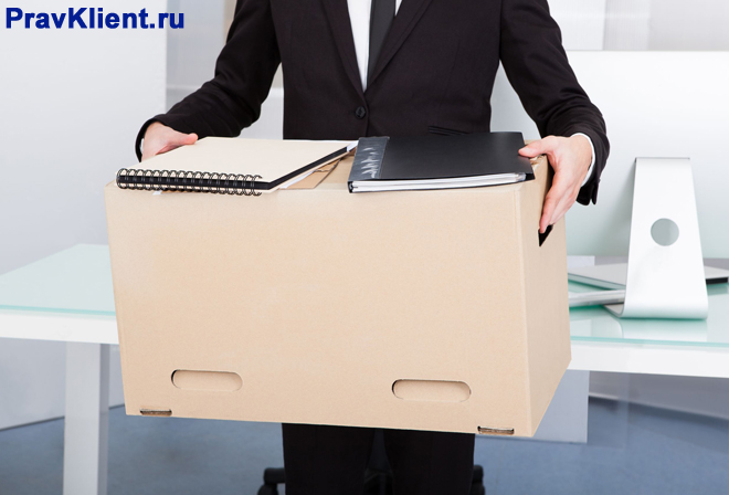 Бизнесмен несет в руках большую картонную коробку