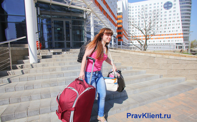 Девушка везет чемодан по лестнице