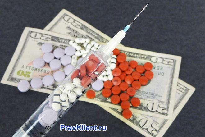 Таблетки и шприц лежат на деньгах