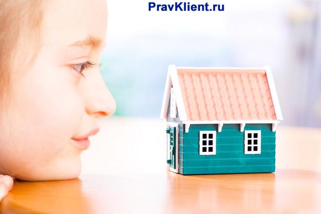 Девочка смотрит на игрушечный домик