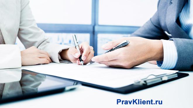 Бизнес-партнеры подписывают в офисе документы