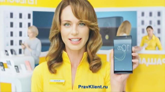 Продавец-консултант держит в руке мобильный телефон