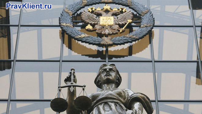 Фемида и герб РФ на фасаде здания
